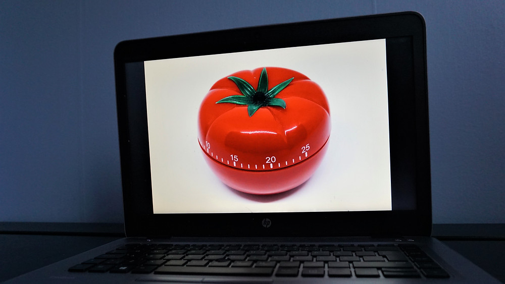 A picture of a laptop in a dark room, with the screen showing a picture of a tomato shaped kitchen timer