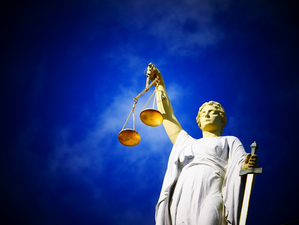 A picture from a low angle of a Lady Justice statue against a blue background.