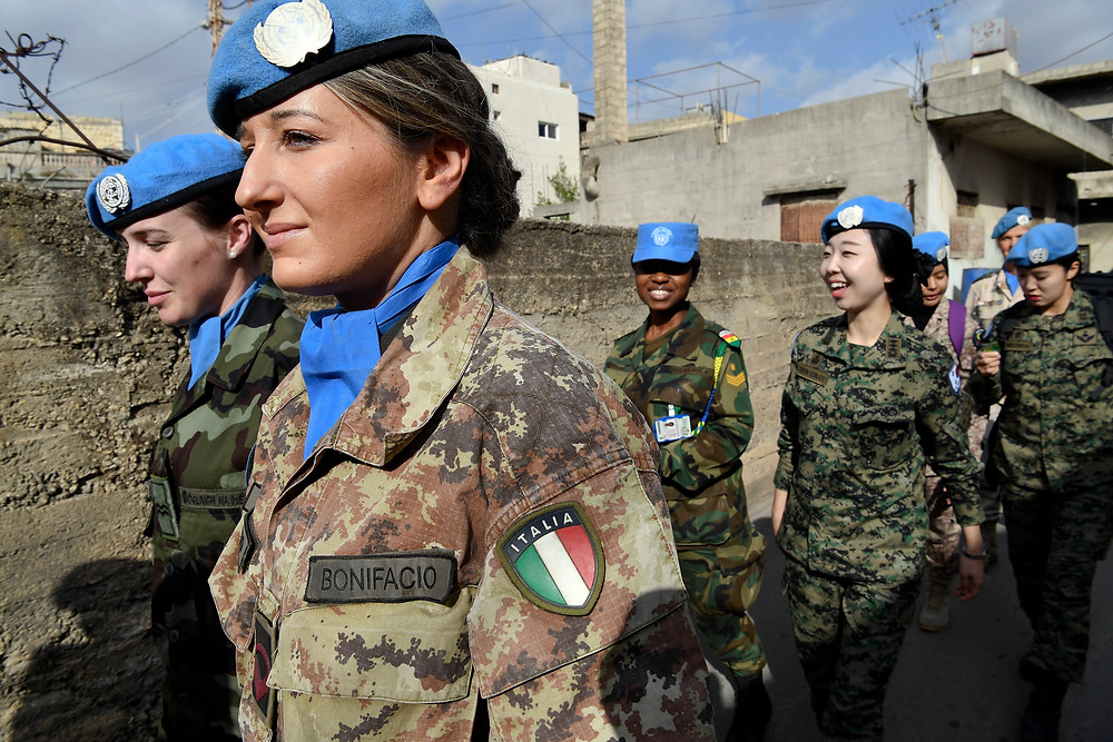 A photo of a group of UN women peacekeepers walking down a street in Lebanon, with a woman from the Italian contingent in the foreground.