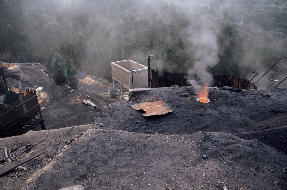 A picture of part of a coal mine, showing dark coloured dirt and gravel in the foreground, with fire coming through a hole, and some wooden structures and rails beyond with a forest in the background