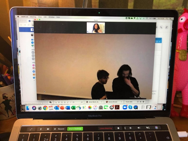 A picture of a video call on a laptop screen, showing two people looking puzzled at a laptop.