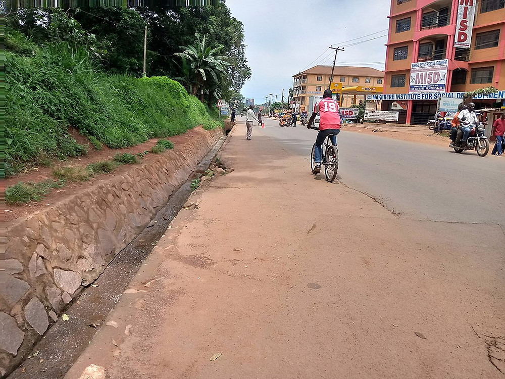 A scene from a street in Kampala with only a few people walking and biking during the COVID lockdown.