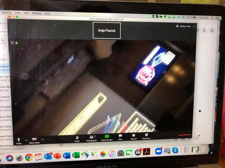 A picture of a video call on a laptop screen, with a very blurry and upside down computer and projector screen visibile in the call.