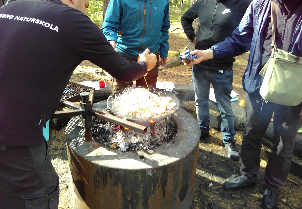 A picture showing a group of people standing around a fire grate outdoors cooking on a pan.