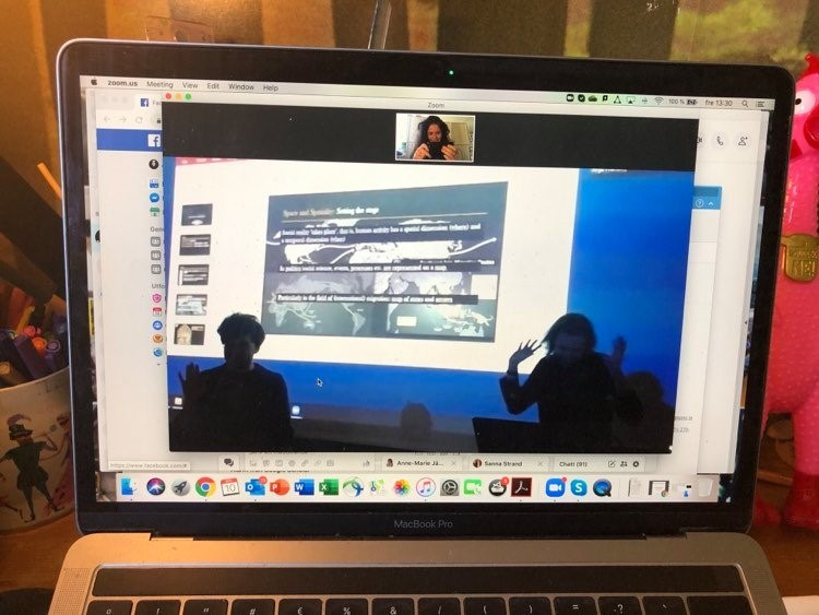 A picture of a video call on a laptop screen, showing two people in front of a projector screen with their hands raised
