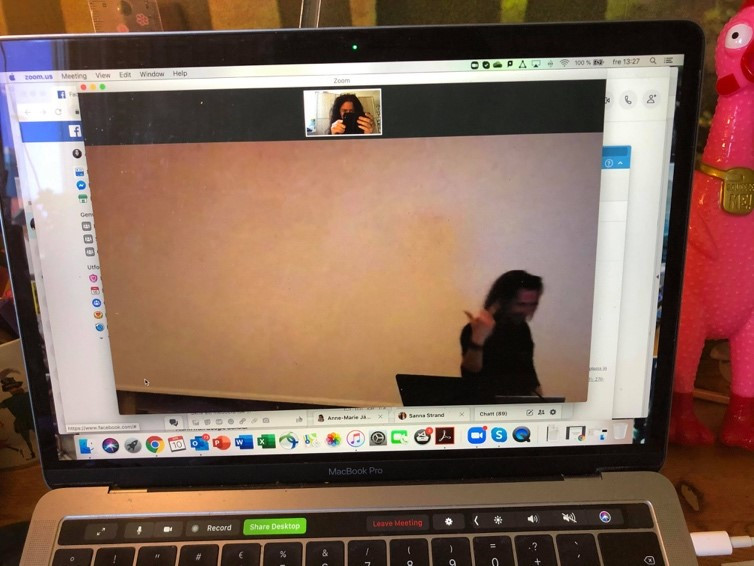 A picture of a video call on a laptop screen, showing one of the two people before giving the finger