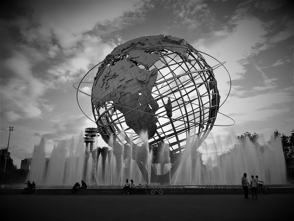 A black and white photo of the Unisphere sculpture in New York, displaying a large metal globe surrounded by fountains.