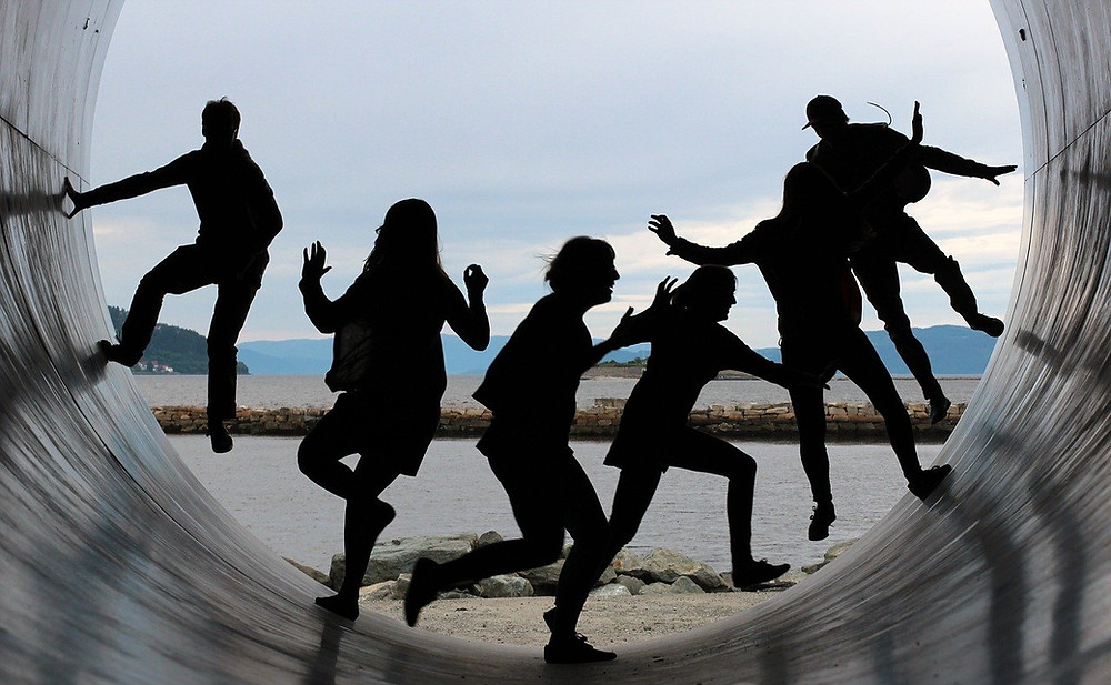 A picture showing the silhouettes of six people climbing on the inside of a large tube with the coast in the background