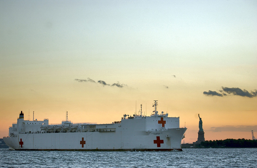 The hospital ship USNS Comfort enters New York harbor with the Statue of Liberty and sunset in background