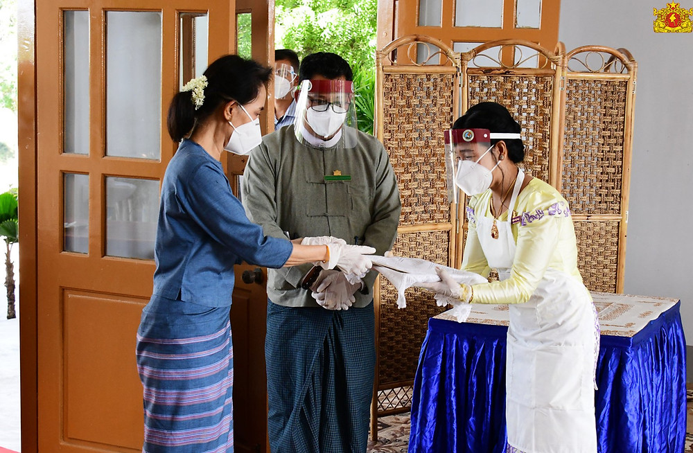 A photo of Aung San Suu Kyi, wearing a mask, handing her ballot to an election worker, wearing a mask and face shield, as another election worker looks on, also wearing a mask and face shield, in front of a brown door, a table with a blue cloth around it, and a wicker screen.