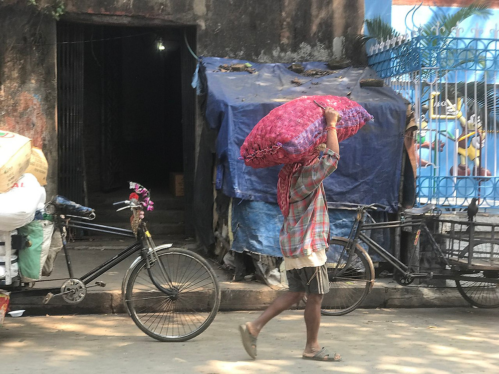 A person carries a bag of food down a street past two bicycles in Kolkata, India during the COVID 19 lockdown.