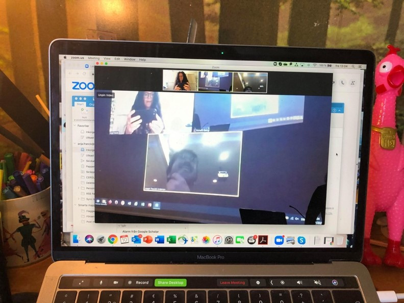 A picture of a video call on a laptop screen, showing the call projected on a screen in the call.