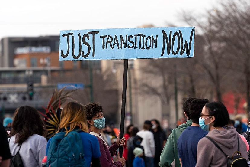 En kvinna håller ett 'Just Transition Now'-plakat på en demonstration i Minneapolis.