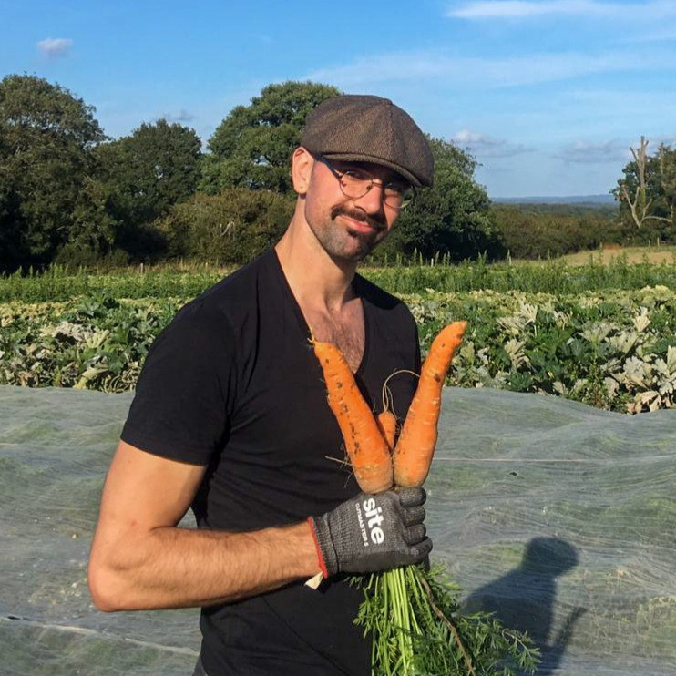 A picutre of Theo Aalders holding a bunch of carrots