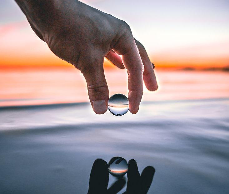 En hand hållande en droppe över havsytan i en solnedgång.