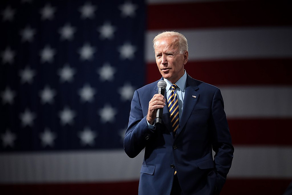 A picture of Joe biden in a blue suit holding a microphone in front of an American flag backdrop