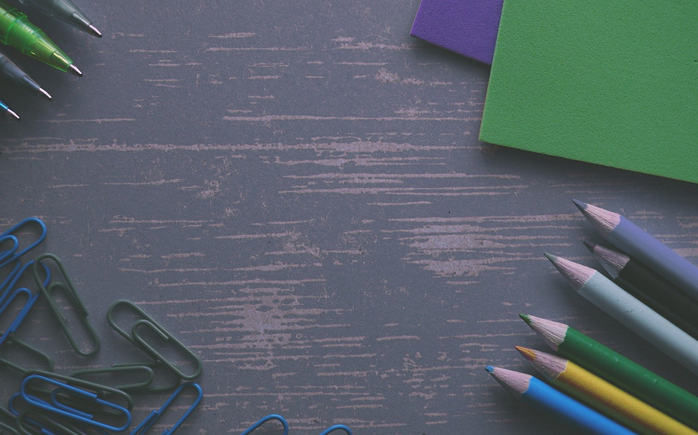 A picture of a grey table top from directly above, with colored pencils in the lower right, coloured paper in the upper right, pens in the upper left, and paper clips in the lower left.