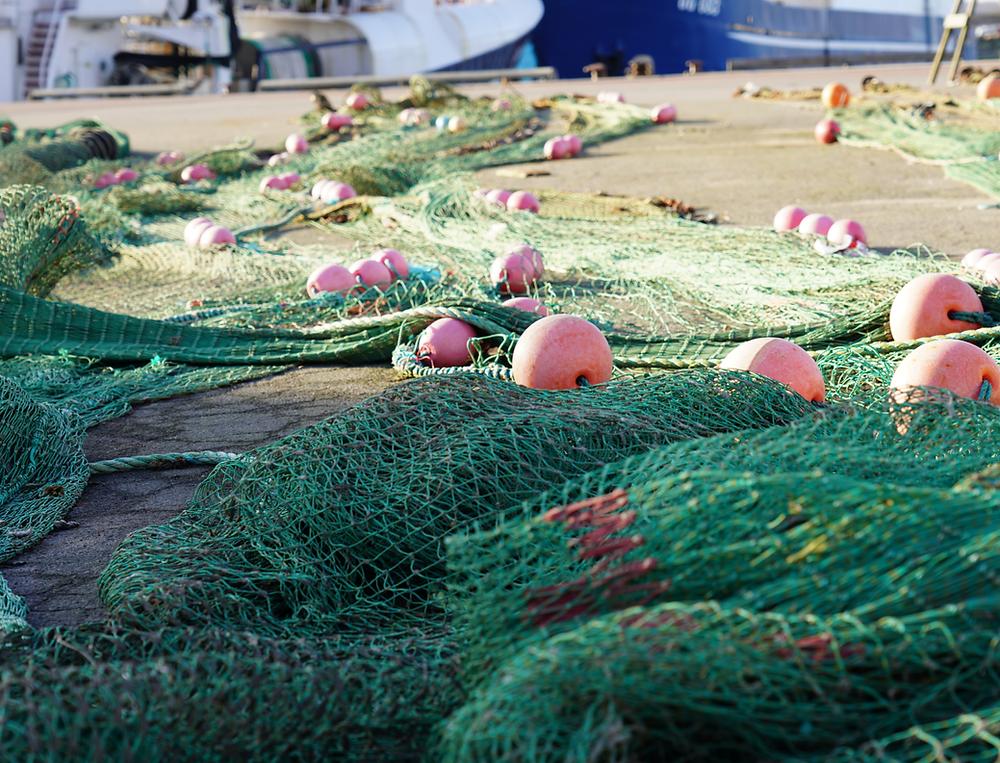 Fiskeredskap på kajen med fiskebåt i bakgrund.