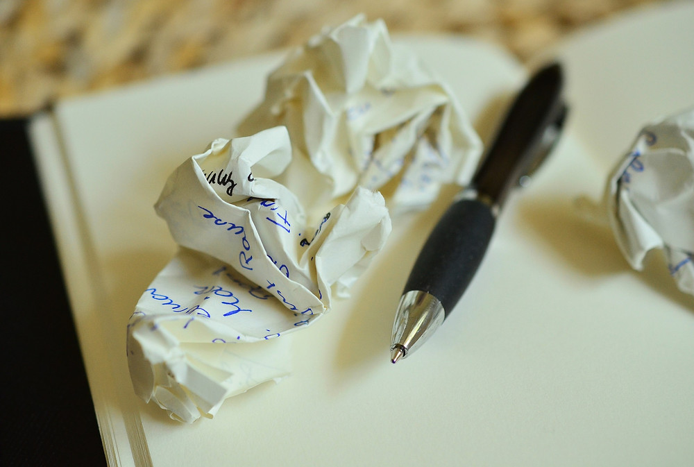 A photo of a crumpled piece of paper next to a pen.