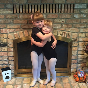 Two child ballet dancers hugging