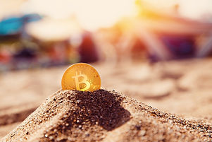 Bitcoin on golden sand, in background se