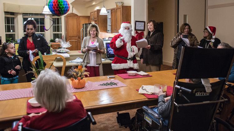 Profissionais, amigos e familiares cantam canções de Natal para moradores em uma Green House.