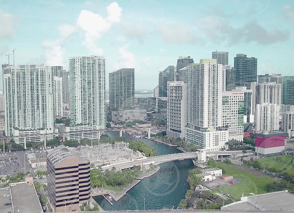 River in the middle of the city of Miami with tall buildings and traffic in the