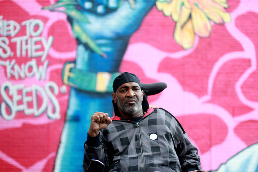 Baba Baxter sits in his power chair holding up Baba's right fist in front of a mural. Baba has dark skin and has salt & pepper facial hair.