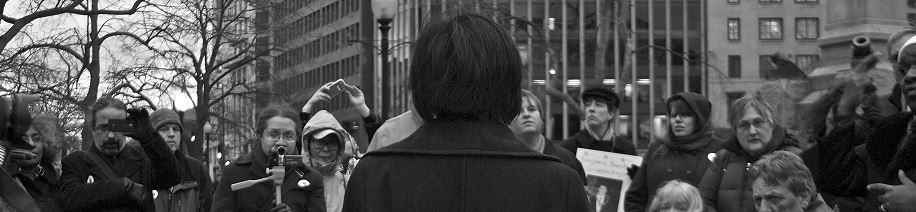 Black and white photo of a the back of a person facing a crowd of people