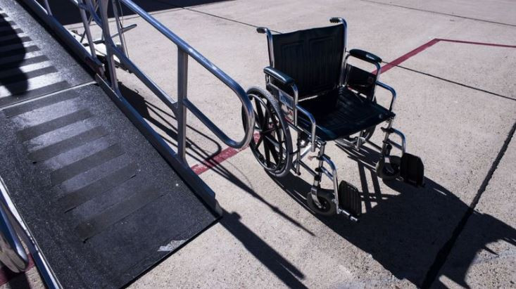 A wheelchair is pictured, located next to a luggage conveyor belt.