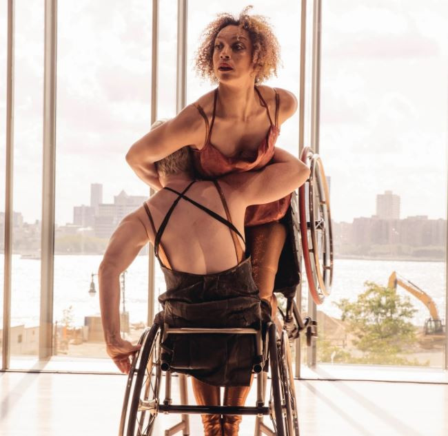 A man facing a window is seated in a wheelchair while lifting a woman who is also seated in a wheelchair.