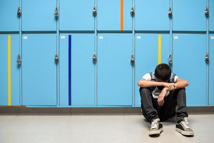 A student sits on the floor in front of blue lockers with arms folded and head down.