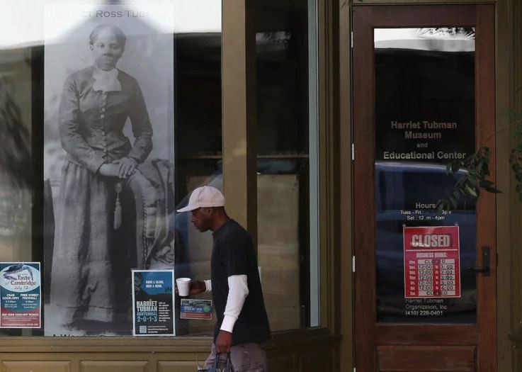 A man in a white baseball cap stands in front of a picture of Harriet Tubman.