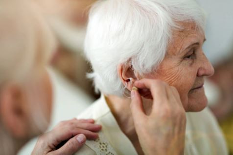 A person is helping another elderly person adjust a hearing aid