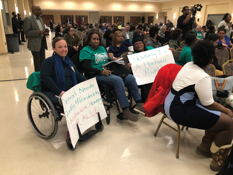 Accessible housing advocates, some sitting in their wheelchairs, holding up signs advocating for housing rights in a crowded community room.