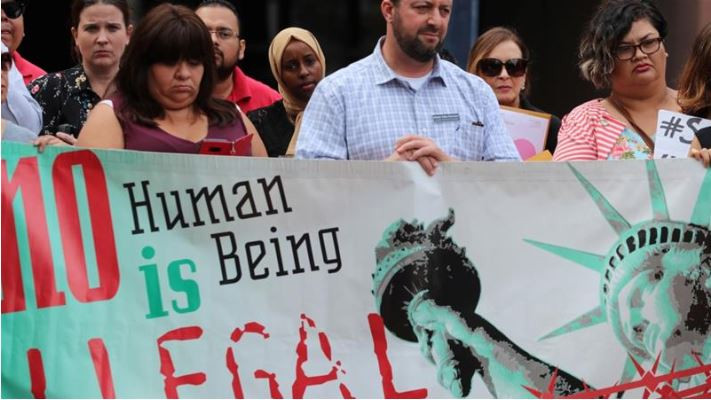"People protest a pending deportation with a banner that reads ""no human being is illegal"", outside the federal building in San Diego, California, US."