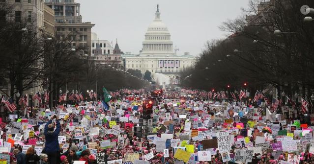 a picture of a large group of protesters in front of the United States Capitol