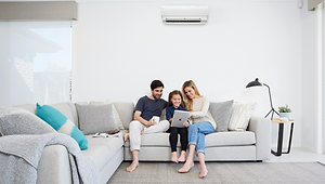 Family sat on sofa with air con unit.png
