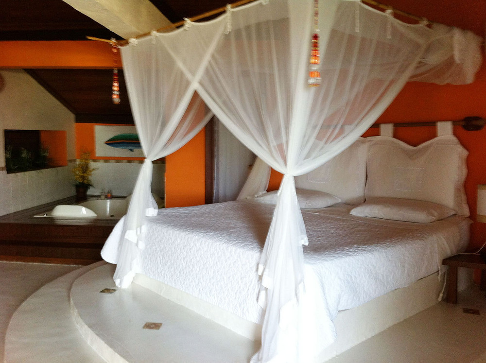 A queen size bed with white sheets and white drapes for privacy