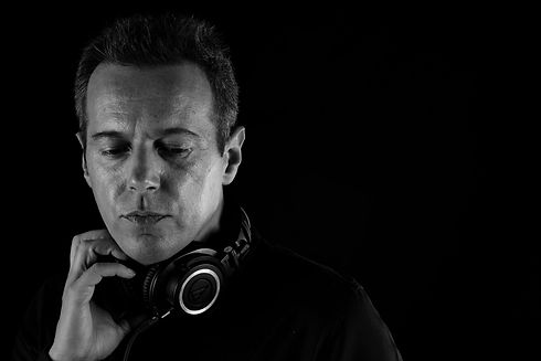 A black and white portrait of the male native Italian voice artist Luca Torchiani while holding a hand on the headphones
