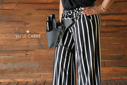Pro hairstylist wearing the Set Walk leather hairstyling holster for organizing hairtools