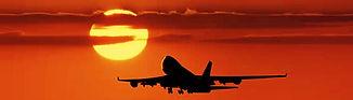 Airplane flying towards sunset