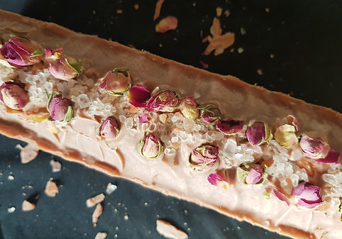 A large block of pink soap decorated with rose petals and salt crystals