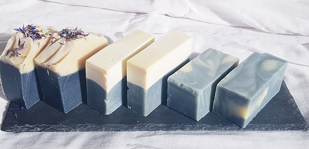 Different types of blue coloured soap bars on a charcoal slate board