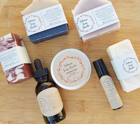 A variety of soap bars, tin of deodorant paste, a bottle of face oil and eye serum on a board