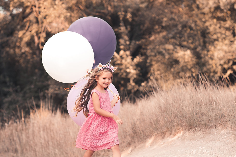 Happy kid girl 4-5 year old running with balloons in meadow. Birthday party. Childhood. .j