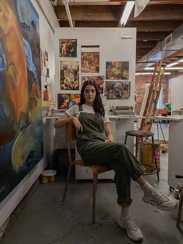 Natasha Verbeke sitting cross legged on a chair in her art studio