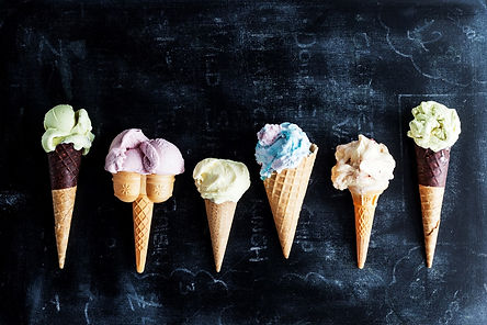 Line up of Ice cream cones all different sizes on a chalkboard background