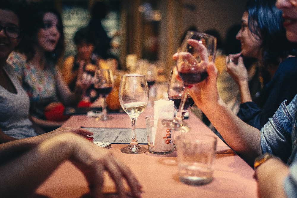 People drinking wine at a gathering.