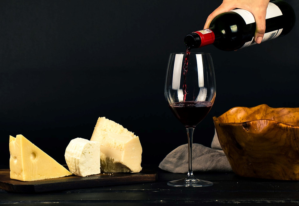 person pouring wine in glass and variety of cheese on the table